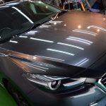 マツダ・アクセラ(マシーングレープレミアムメタリック) PRO PCX-S8コーティング 平成28年登録、走行距離約8,000㎞のお車。今春試乗車をお買い求めになりコーティングのご依頼でした。  マシーングレープレミアムメタリック、しかも高年式車ともあってキレイに見えますが、力の強い光源下では光沢を減少させている事が判ります。  塗装面を平滑化させ更にピカピカにします。